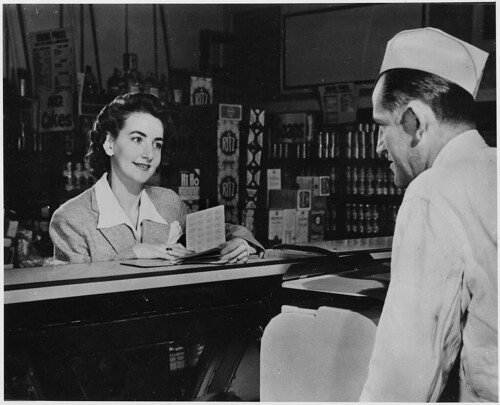 "A Customer Can Use the Ration Books of the Whole Family. But the First Thing She Will Want to Know When She Buys Pork Chops, Pound of Butter or a Half Pound of Cheese Is - ""How Many Points Will It Take?"" 1941 - 1945 