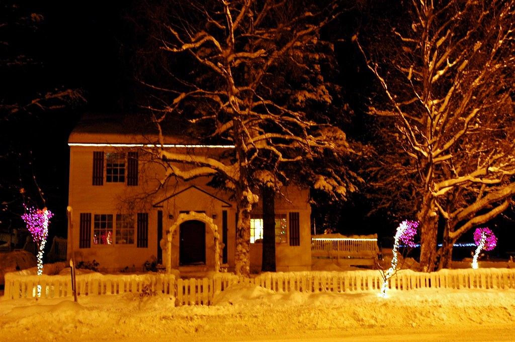 saltbox house with christmas lights on trees pink and white picket fence arbor arch