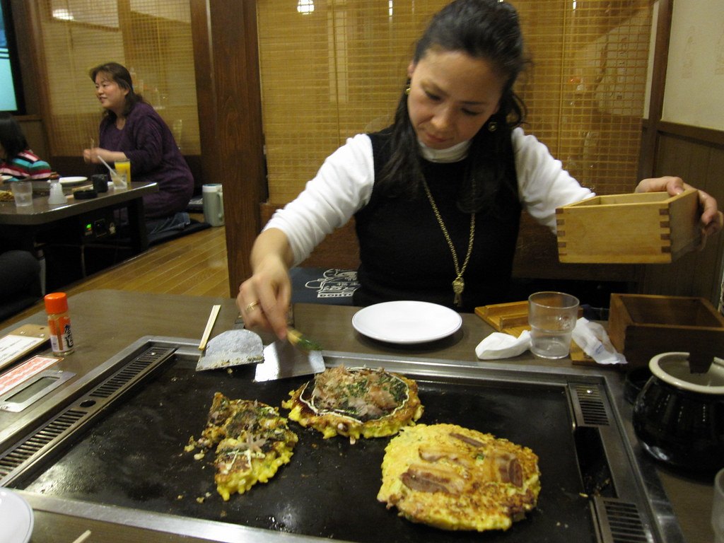 An okonomiyaki restaurant patron makes her own okonomiyaki