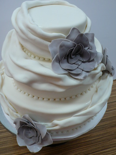Draped White Fondant Stash Wedding Cake with flowers | by CAKE Amsterdam - Cakes by ZOBOT
