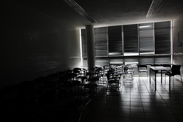 "The photograph ""Classroom"" by Esparta Palma shows a dark and empty classroom, with light barely coming in through closed venetian blinds."