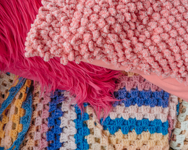 pink cushions on crochet blanket