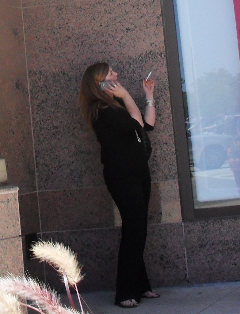 Woman Smoking A Cigarette At An Outdoor Shopping Mall In N -6370