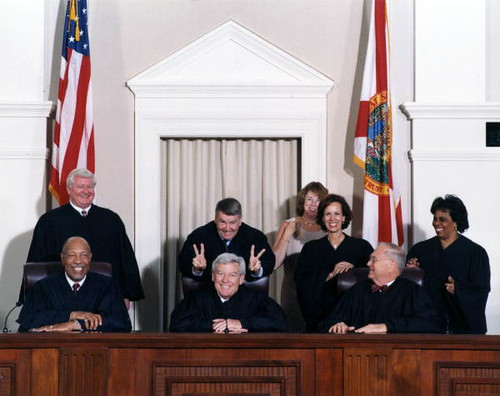 "Harry Anstead putting ""rabbit ears"" on Charles Wells prior to formal en banc portrait of Florida Supreme Court Justices from the year 2000 