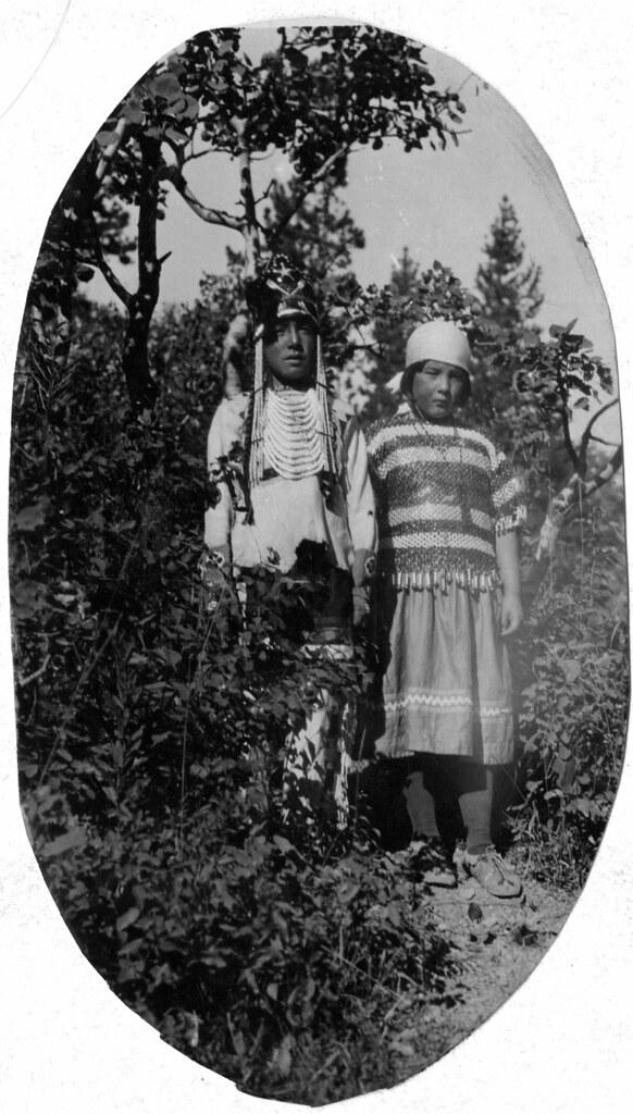 Nativo americano maschio e femmina che sta sul monticello nella parte anteriore-6998