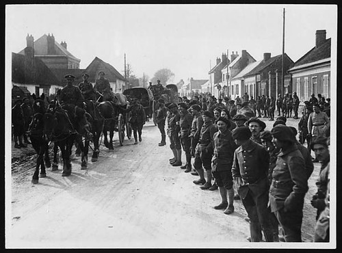 French troops lined up watching British Artillery passing through a village | by National Library of Scotland
