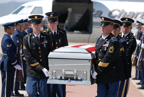 Arizona Guardsmen carry the casket of a fallen Soldier past his family at Luke Air Force Base, Ariz. | by The National Guard