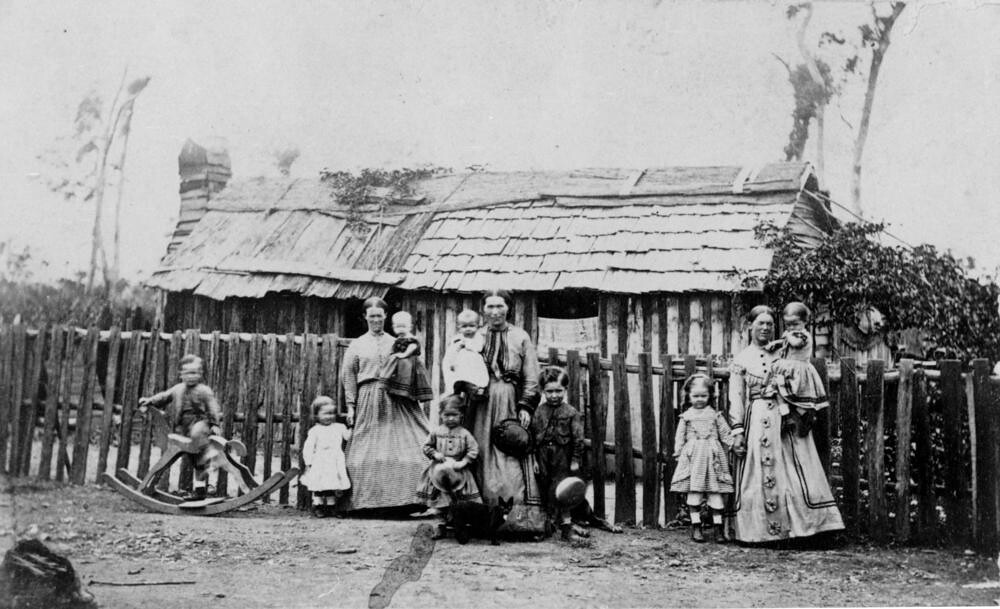 Mothers And Their Children Standing Outside A Bark House