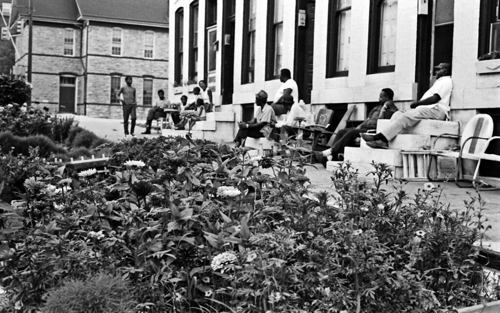 People sitting on rowhouse steps.