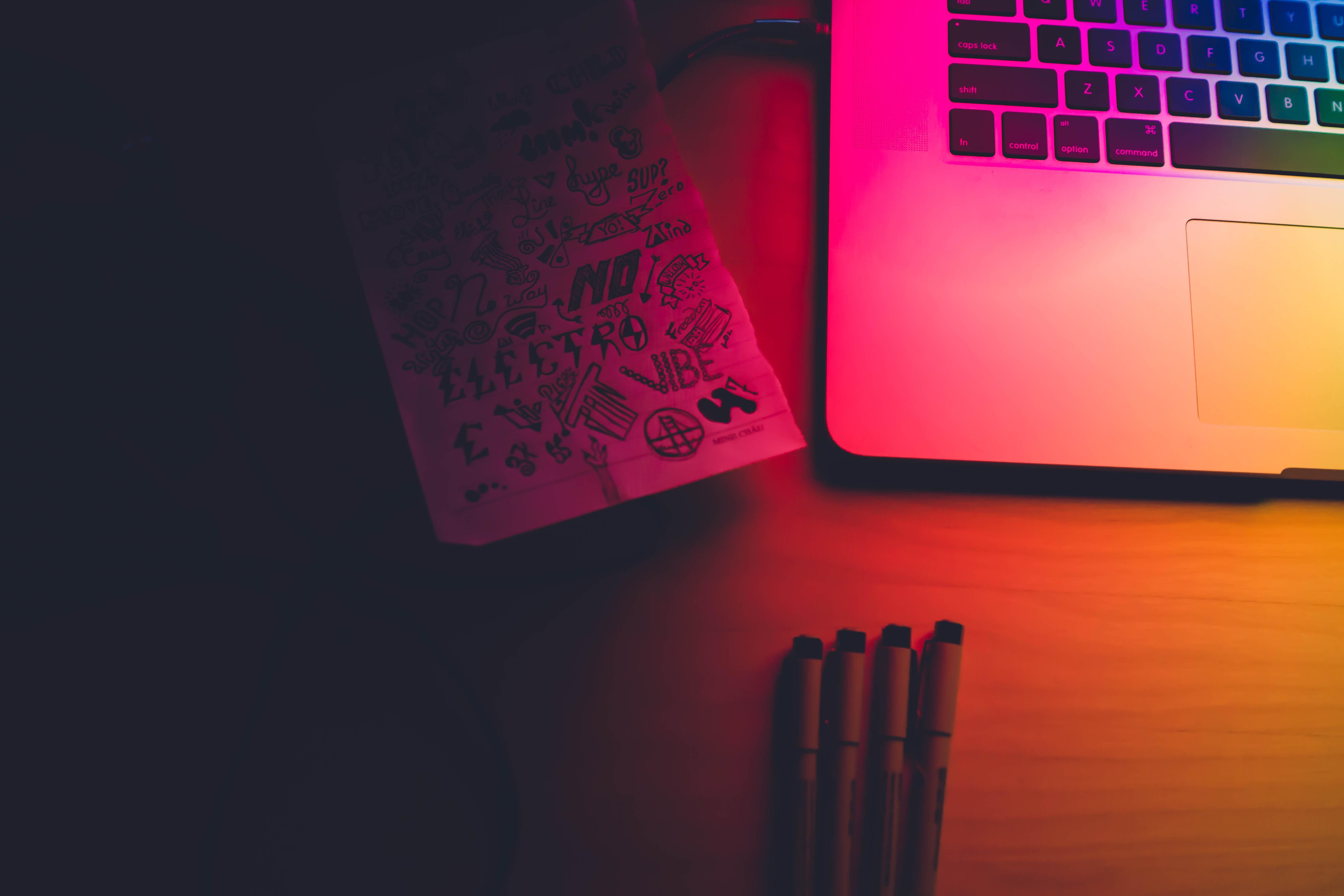 Night sketches near a laptop keyboard under rainbow lighting.