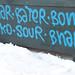 Blue graffiti tags on a newspaper stand