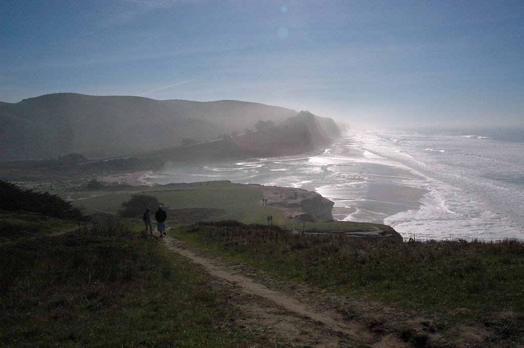 A couple walking on a Pacific Ocean beach, mist on cliffs ...