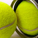 Two tennis balls out of their plastic tube