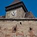 Saxon church tower with clock behind defensive walls