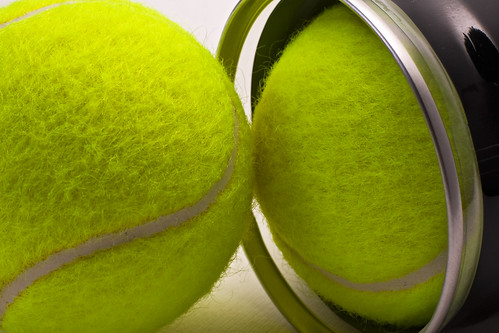 Yellow tennis balls out of black container | by Horia Varlan