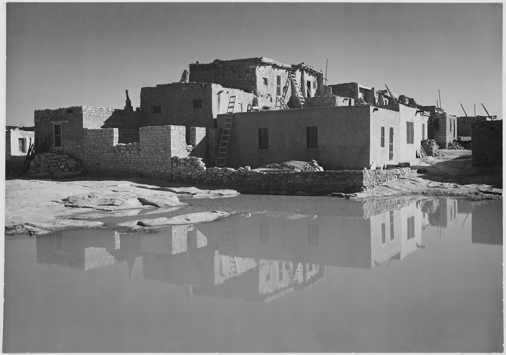 Full side view of adobe house with water in foreground a for Building houses with side views