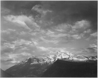 "Dark foreground and clouds, mountains highlighted, ""Heaven's Peak,"" Glacier National Park, Montana. 