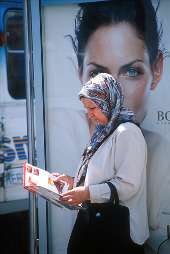 A woman read a magazine while waiting for a bus | by World Bank Photo Collection