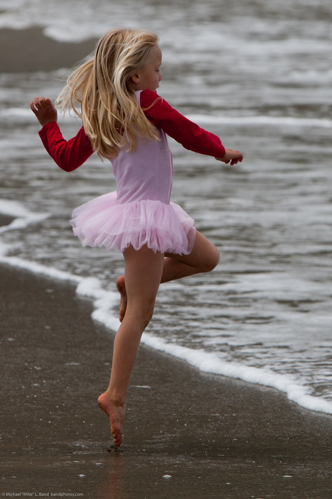 Cute Little Girl In Pink Dances On Beach During The Kite F -4094