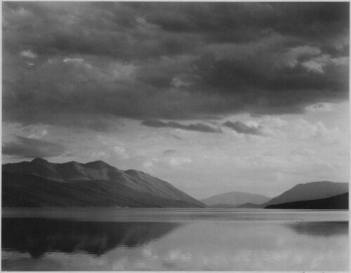 "Looking across lake to mountains and clouds, ""Evening, McDonald Lake, Glacier National Park,"" Montana. 