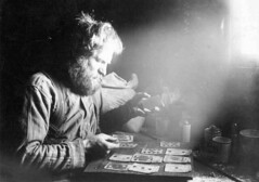 Charles Ainsworth playing cards inside cabin at 60 Above on Sulphur Creek, Yukon Territory | by UW Digital Collections