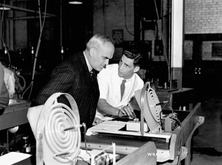 C.D. Howe watches a scientist test the curve of a lens, Instruments Division, Canadian Arsenals Ltd. / C.D. Howe observe un scientifique qui vérifie la courbure d'une lentille, Division des instruments, Arsenaux canadiens Ltée | by BiblioArchives / LibraryArchives