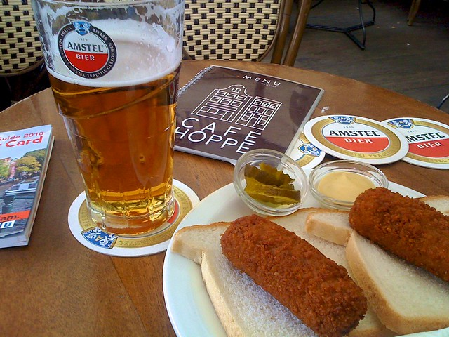 Dutch kroketten with bread and a glass of beer on a cafe table