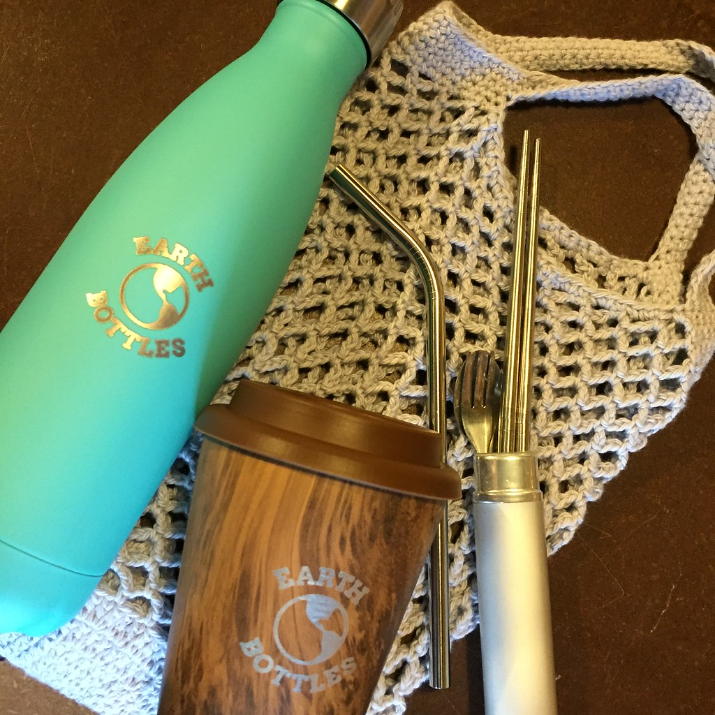 a little collection including a reusable coffee cup, a stainless steel water bottle, a stainless steel straw and cutlery set and a crocheted mesh bag