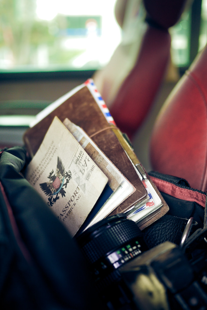 Travelers Notebook And Camera On Big Red Airport Bus Couch