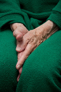 Old woman's hands tucked between her legs | by Horia Varlan