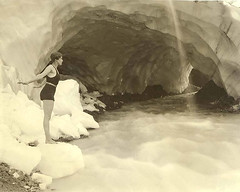 Woman in bathing suit at edge of stream near Paradise Glacier ice cave, Mount Rainier National Park | by UW Digital Collections