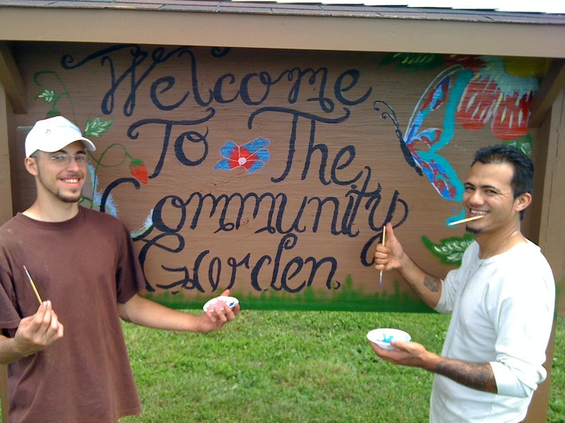 men painting sign in community garden