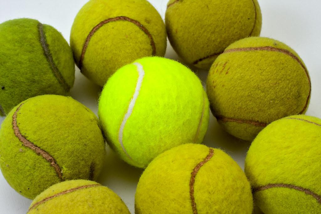 Brand New Tennis Ball Among Eight Used Ones Brand New
