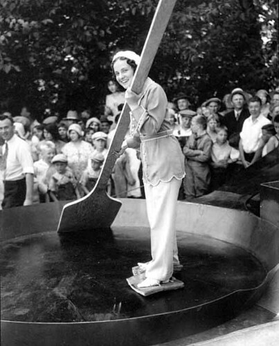 Woman with slabs of bacon tied to her feet standing in a giant skillet holding an enormous wooden spatula and smiles at the crowd, Chehalis, Washington | by UW Digital Collections