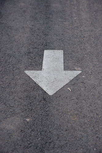 White arrow on gray tarmac | by Horia Varlan