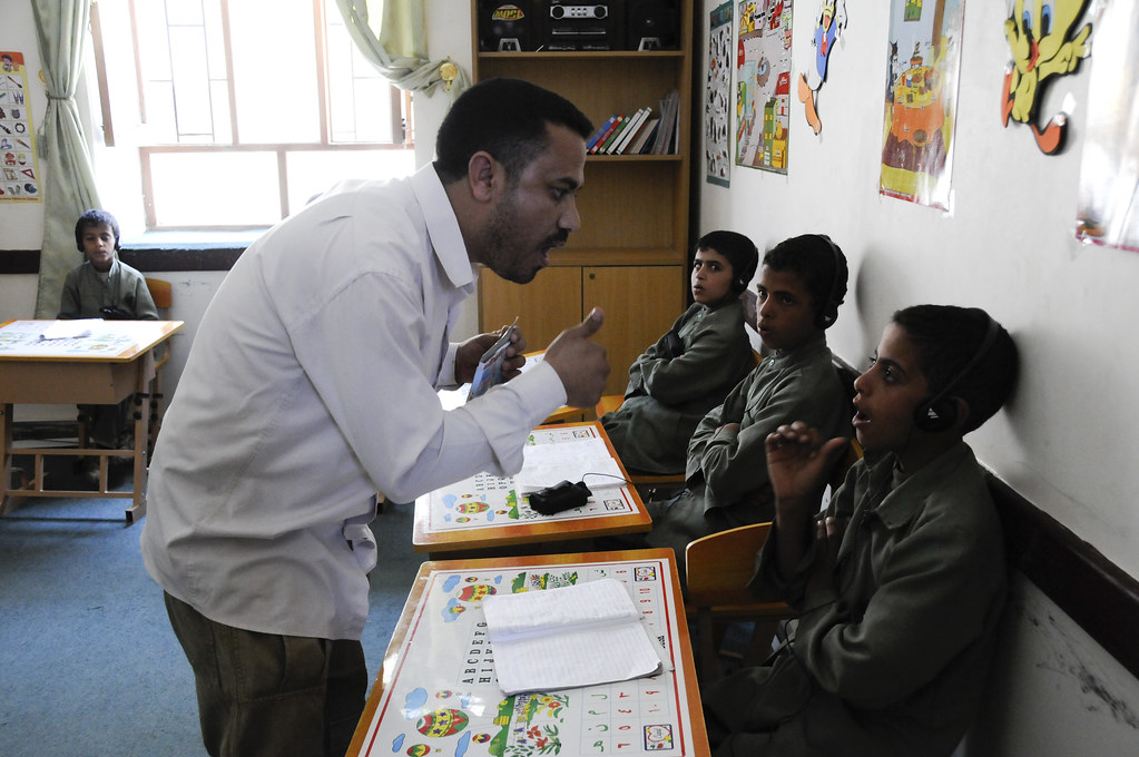 a teacher works with a hearing impaired student