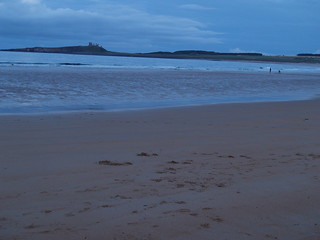 Surfers and Dunstanburgh Castle from Low Newton / Embleton | by Experience North Country