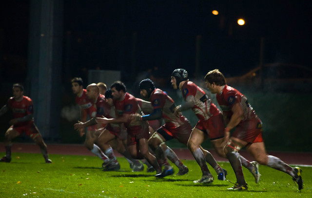 Rugby players charging ahead on the field
