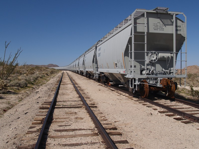 A string of train cars used for hauling sand sit on a siding at Dos Cabezas
