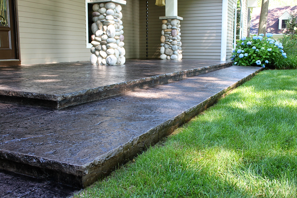 Seamless stamped concrete sidewalk with hand tooled border for Granite overhang