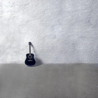 Untitled picture of a guitar leaning against a wall | by thomas bach nielsen