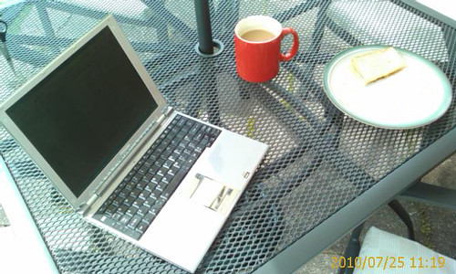Laptop and working lunch. An outside table with a silver laptop, coffee and a sandwich on it. | by Rob Pearce