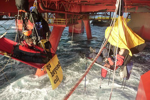 PIC: Sim and Timo doing morning stretches suspended from the rig #beyondoil | by Greenpeace UK