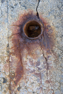 Rusted metal pipe in cracked concrete | by Brian Reynolds