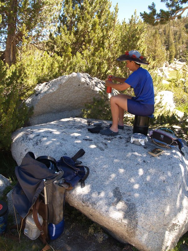 Vicki makes some ramen noodles for lunch, sitting on a big boulder in the shade