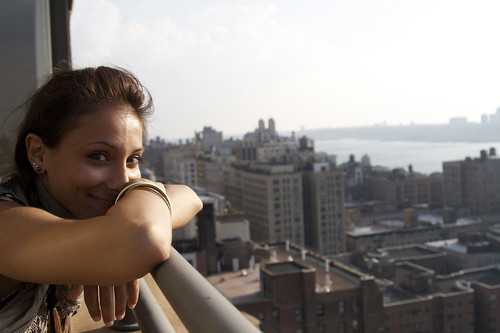 A smiling person leaning on a balcony railing.
