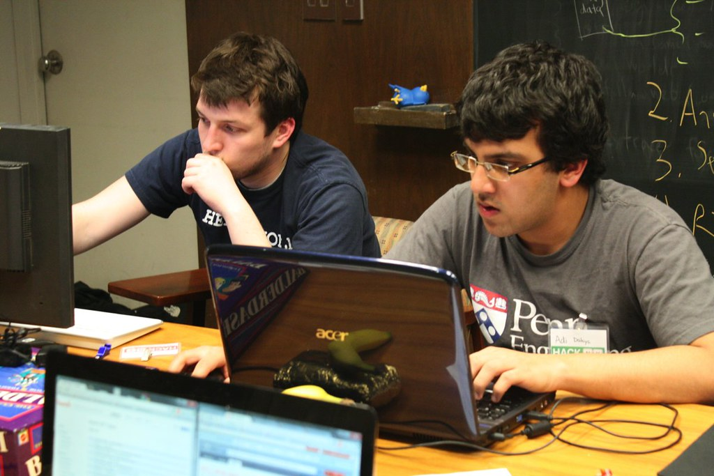 two students sitting in a classroom and working on their laptops