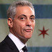 "Chicago Mayor Rahm Emanuel forming the letter ""f"" while looking sideways, while standing in front of the Chicago flag."