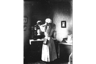 Unidentified woman trying on hat in front of mirror, Washington | by UW Digital Collections