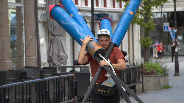 Scott Flanary carries large, imitation fireworks on a city street.